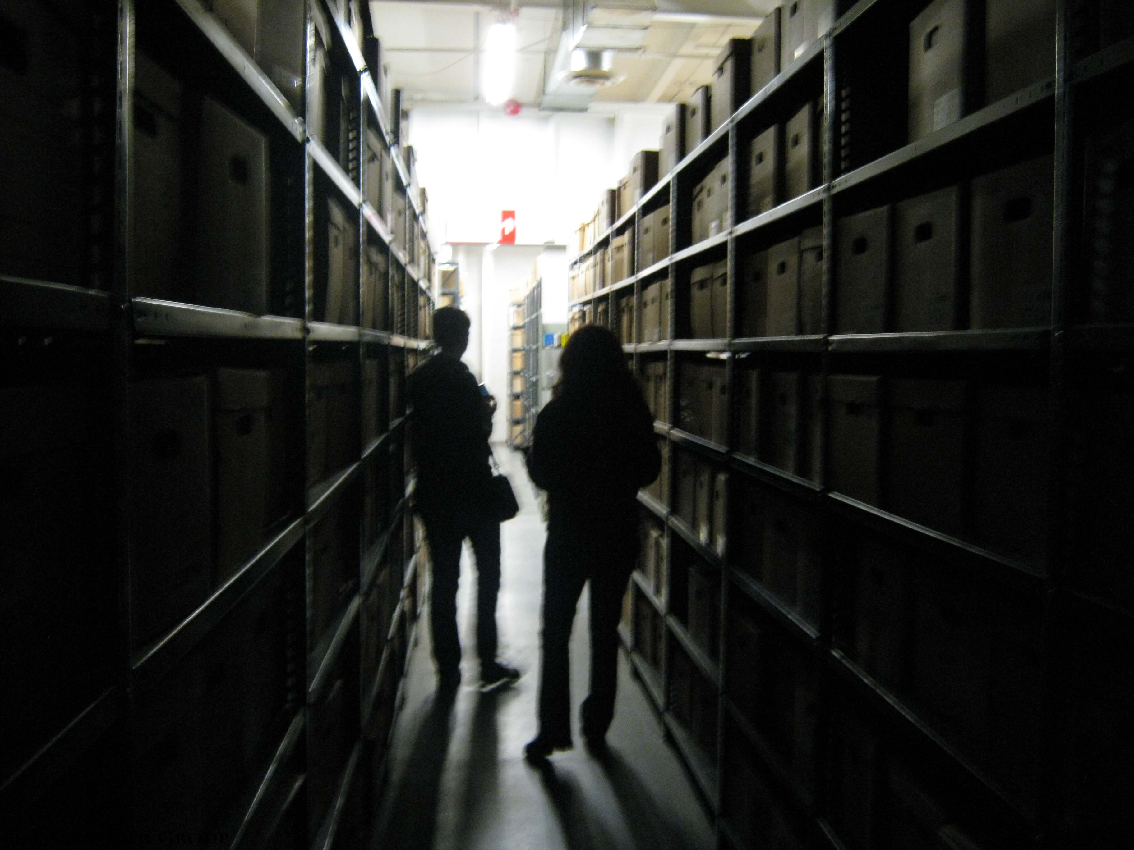photo of two The Searcher Group team members Investigating the CNE Archives walking through the aisle with shelves of boxes on either side