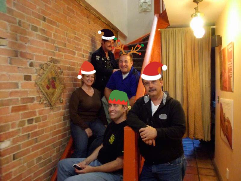 Richard, Peter, Paul, James and Victoria with Christmas Hats posing on staircase