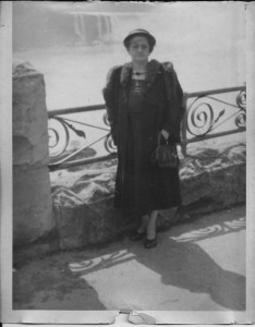 black and white photo of lady standing in front of a fence